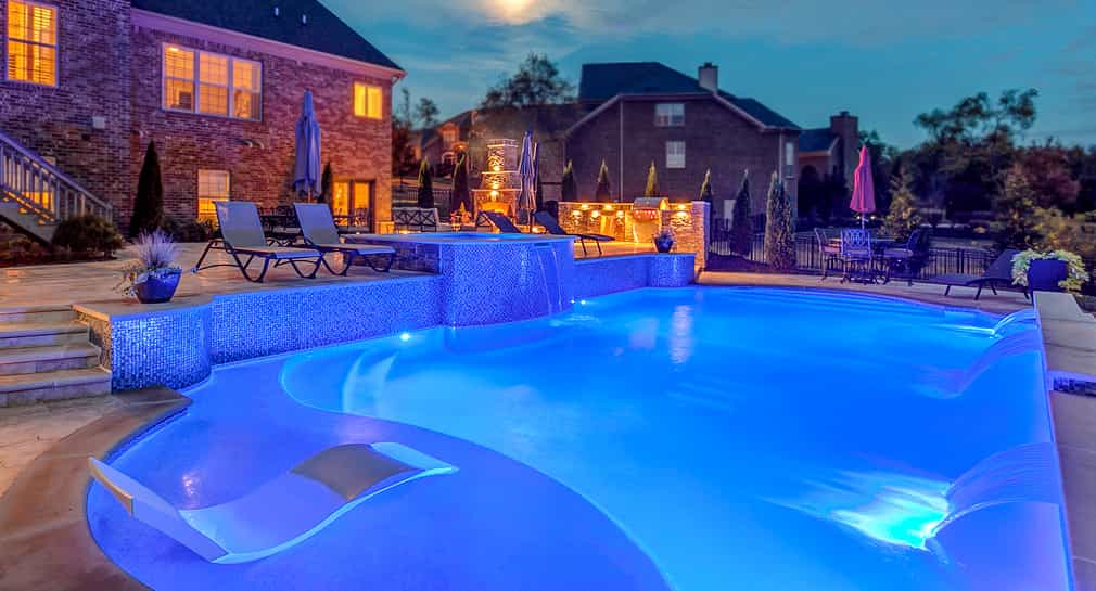 Formal pool with custom lighting, a sundeck and kitchen