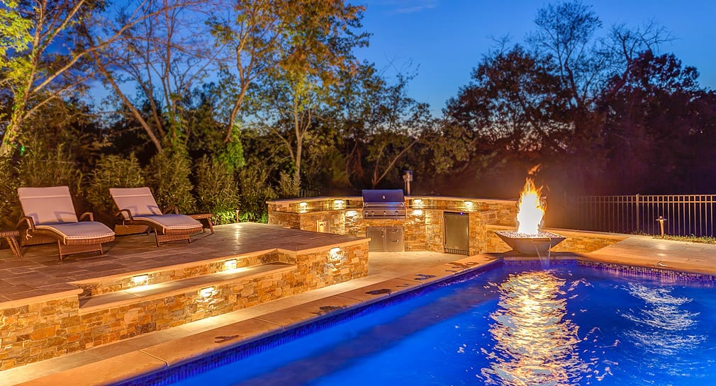 Outdoor kitchen with fireplace and pool