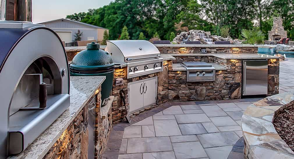 Outdoor chef's kitchen with grill, smoker and pizza oven