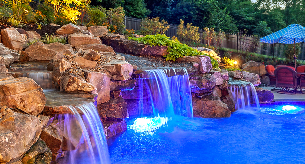 Triple water fall, lighting, natural stone landscaping around a custom designed pool